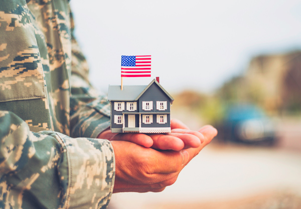 Solider Holding A Model House with American Flag